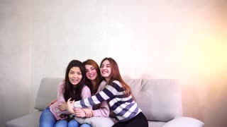 Charming women in good spirits looking into camera, talk to each other, laugh and smile, sitting on background of gray wall in bright room. Concept beautiful and happy girls, good mood and bright