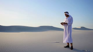 Cheerful Arabian Sheikh male tourist calls friend on Videocall by cell and shows surroundings of white sand desert on hot day