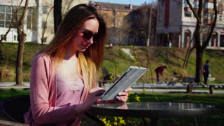 Cheerful female person resting in park with tablet and chatting with friends. Concept of free hotspot and fast wireless Internet in rest zone. Young woman having break on fresh air.