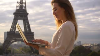 Cheerful female person using laptop with Eiffel Tower background and looking at camera with smile. Concept of working freelancer in France. Young woman wears white blouse.