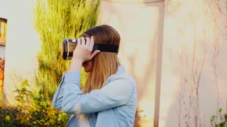 Cheerful girl enjoying with virtual reality headsets near green plant. Concept of using modern gadget in free time. Young woman wears jeans shirt.