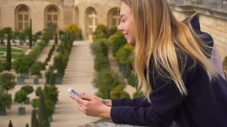 Cheerful woman chatting by smartphone with Versailles background in slow motion. Concept of visiting France heritage attractions and trip to Europe. Young female person resting with new gadget in