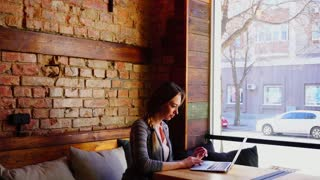 Cheerful young female person chatting with guy by laptop at cafe. Concept of online communication by computer and wireless free Internet. Pretty woman wears sweater and blouse.