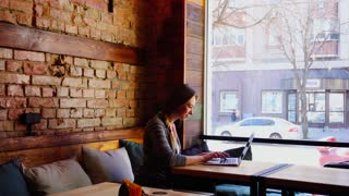 Cheerful young woman typing message in social network near large window at cafe. Concept of resting with free hotspot and having break. Beautiful dressed in casual clothes resting near brick wall.