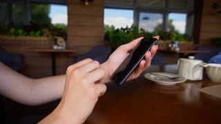Close up female hands using smartphone at restaurant