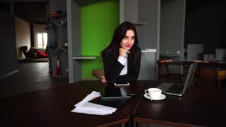 Confident attractive girl, employee of company thought with smile on face and stares into distance in front of her, leaning head against arm and continuing to work behind laptop, sitting at modern