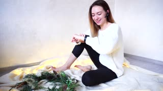 Confident girl chatters and communicates through bluetooth and looks at smart watch watches that are worn on hand. Woman arranges meetings or completes business affairs on eve of new year and sits on
