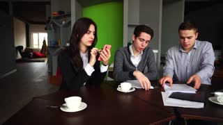 Confident in themselves educated employees of women's firm and two men check and agree documents on payments, study documentation and girl uses smartphone. Colleagues discuss and communicate on topics