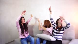 Cool girls celebrating party, dancing at home. Female friends tell gossip and having fun. Concept of beautiful and happy women friends, pleasant pastime for watching movies, hen party and cheerful