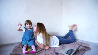 Cute and funny young mother with little daughter communicate, hug and on family kiss. little girl cranks and shows tongue in camera, fools around and tangles hair, sitting on floor in bright room