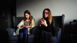 Cute female employees of company busy with their own affairs and keep smart phones in their hands, correspond with social networks or read news, sitting in gray comfortable chairs in stylish cafe on