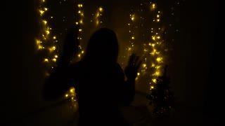Dancing girl silhouette and twinkling garlands