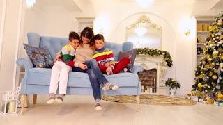 Diligent mother of two twin boys and children sit side by side and in family way embrace on blue sofa in festive decorated room with Christmas tree and fireplace in afternoon