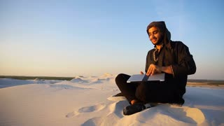 Educated Arab student uses laptop and works sitting on sand amid sand dunes of desert on warm summer evening