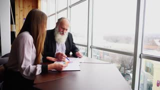Elderly Boss Man Signs Document With Young Assistant With Papers in Office.