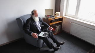 Elderly Smart Man Quietly, Slowly Sings and Looking at Text on Laptop and Sitting in Chair in Room.