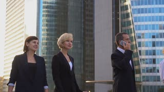 Employees of business corporation passing in slow motion and talking by smartphone