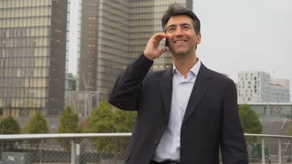 European businessman walking and speaking by telephone