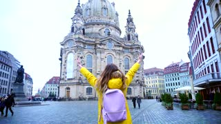 Fascinating female happy from location and delighted with sights of city. Girl raises hands up, whirls around and jumps, smiling with happiness. Young European-looking woman with long fair-haired hair