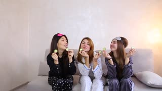 Fashionable and beautiful girls have fun together and share beauty secrets, make fresh face masks and relieve tired eyes by putting pieces of cucumbers, laughing and relaxing in bright bedroom in