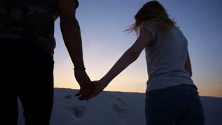 Female and male holding hands together rise to top of sandy hill in desert against blue sky at sunset on warm evening