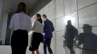 Female and Male Office Worker go Back to Camera and Talk About Working Paper on Background of Wall of Business Center Outdoors in Neutral Colors.