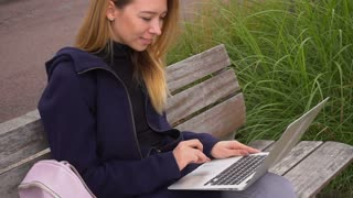 Female person sending message by laptop and sitting on bench near green grass. Concept of chatting with free hotspot in park and resting. Happy student having free time outside with computer.