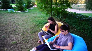 Female Sales Managers do Not Have Time to do All Work and Quickly Type on Computer Keyboard Sitting in Park Outdoors in Soft Chairs in Daytime.