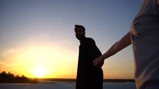 Follow me Arab guy and European woman who walks by hand in desert at sunset on summer evening