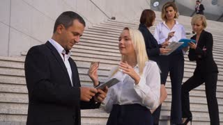 Foreign business colleagues in official journey talking and keeping tablet and cases on stairs