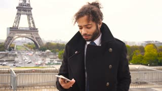 Foreign student in Paris calling with smartphone near Eiffel Tower in slow motion