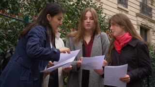 Foreign students learning English with papers near university building in slow motion