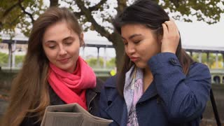 Foreign students looking for flat with newspaper outside