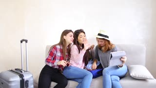 Funny female friends together collect large gray and blue suitcases, add up all necessary things for class holiday in another country on sea. Young women fool around and laugh, measure glasses and