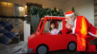 Funny Santa Claus playing with little princes waving hand in red car