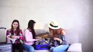 Funny travel friends together collect large gray and blue suitcases, add up all necessary things for class holiday in another country on sea. One European-looking girl with medium-length blond hair
