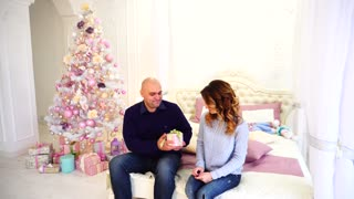 Gift of gifts from husband and wife, happy married couple in festive mood, sit on bed in bedroom with Christmas tree