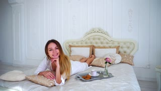 Girl Model Smiling at Camera Lying on Bed in Bright Bedroom.