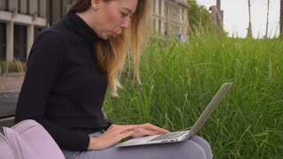 Gladden female person buying online with tablet in park, sitting on bench. Concept of payment by credit card in Internet and shopping. Young woman wears black turtleneck sweater.