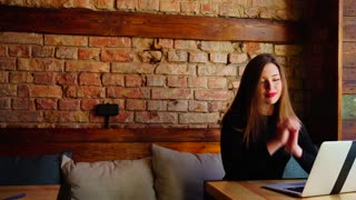 Gladden girl winning bets online by laptop at cafe near brick wall. Concept of sports betting and positive emotions. Young woman has red lips.