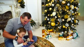 Good Father And Little Girl Spend Time And Holding Gadget Sitting on Floor in Large Room on Background of Decorated Christmas Tree and Fireplace
