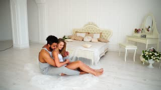 Good-Looking Loving Hearts, Bride and Groom Woke up in Morning Together and Gently Hug and Kiss Each Other, and Sit on Floor. Arab Man With Dark Hair and Beard, Dressed in Pajamas