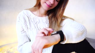 Good-looking Young Woman tunes and tests gadget that is worn on arm. Woman smiles and leads finger along small touch screen of modern electronic clock. European-looking girl with long blond hair is