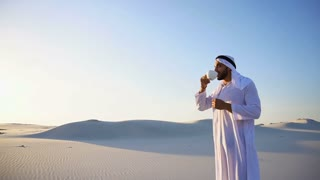 Good morning for male sheikh in middle of huge desert over cup of coffee against blue sky and dunes in open air