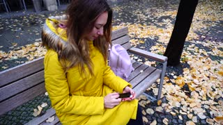 Grand Young woman thumbs and browses on gadget photos with excursions and city sights, sits on bench amidst yellow foliage outdoors on cool autumn day. Young European-looking woman with long blond