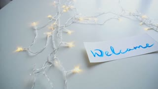 Greeting card with blue calling inscription welcome, painted with watercolors on white rectangular sheet of paper, which lies on light table with flickering garland. Concept of calligraphy and