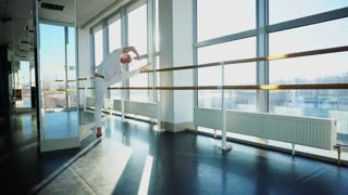 Gymnast in sportswear training near ballet barre in sport gym