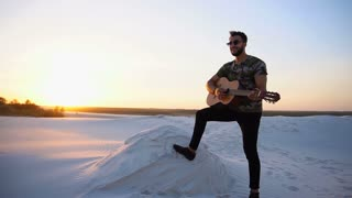 Handsome Arabian guy playing guitar, standing on hill among sandy desert at sunset in open air on warm evening