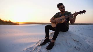 Handsome Arabian young man adjusts guitar, sitting on hill in middle of desert at sunset in open air on warm evening