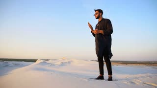 Handsome male Arab businessman talks on cellular business pro, standing in middle of sandy desert in open air on summer evening